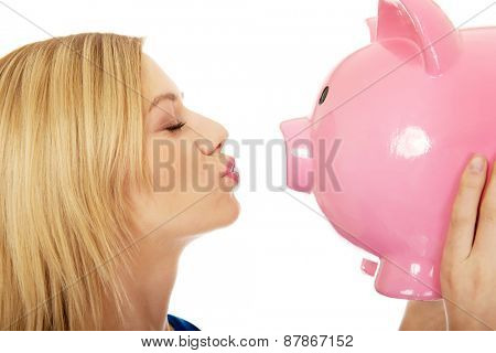 Happy young woman kissing piggybank.