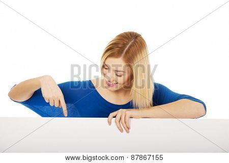 Young happy woman pointing on blank board.