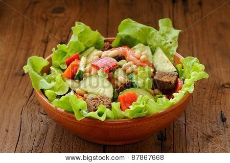 Vegetable Salad With White Beans, Rye Toasts, Tomatoes, Cucumber And Letuce In Clay Bowl On Wooden B