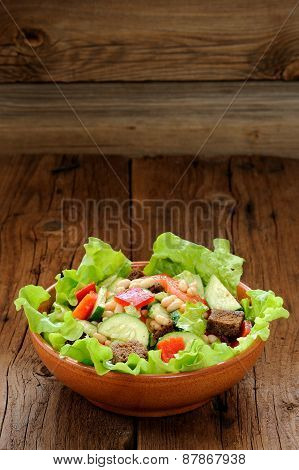 Vegetable Salad With White Beans, Rye Toasts, Tomatoes, Cucumber And Lettuce In Round Bowl On Wooden