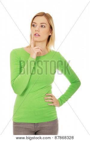 Young thoughtful woman touching chin.