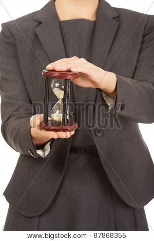 Business woman hand holding hourglass.