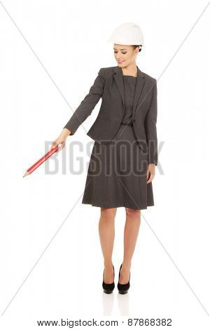 Businesswoman in hard hat pointing down with pencil.