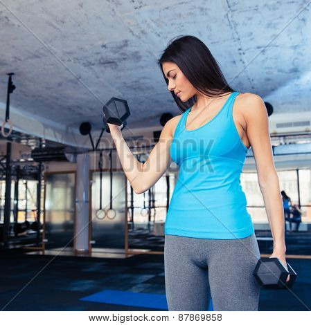 Cute woman working out with dumbbells at gym