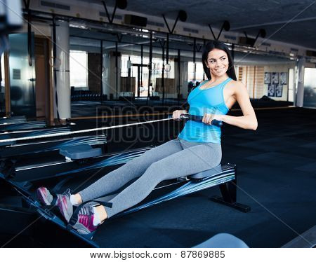 Smiling young woman working out on simulator at gym and looking away