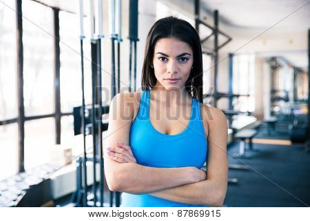 Beautiful fitness woman with arms folded standing in fitness gym