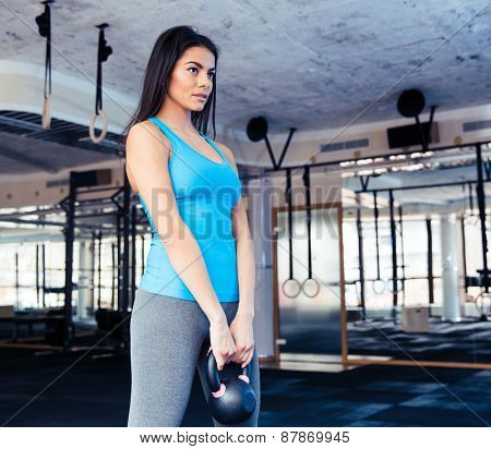 Beautiful woman working out with weight at gym. Looking away.