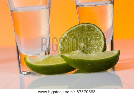 Tequila Shot With A Slice Of Lime On The Glass Orange Background