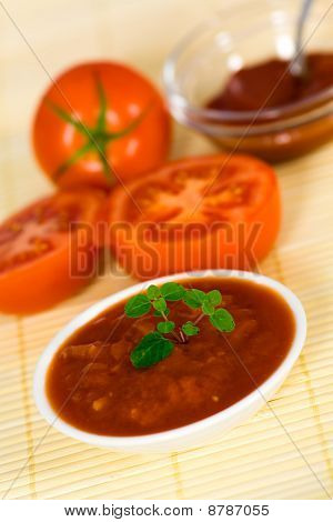 tomato sauce with oregano leaf on a wooden background and with soft shadow