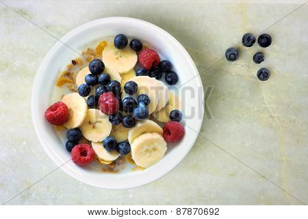 Breakfast cereal with fruit on white granite background