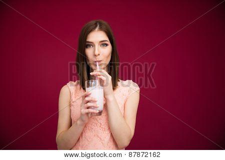 Beautiful woman drinking yogurt over pink background. Looking at camera