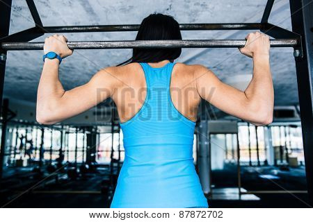 Back view portrait of a fit woman working out at gym