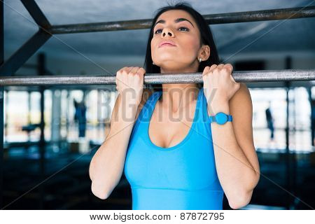 Charming woman working out on horizontal bar at gym