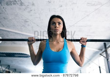 Beautiful fit woman working out with barbell at gym