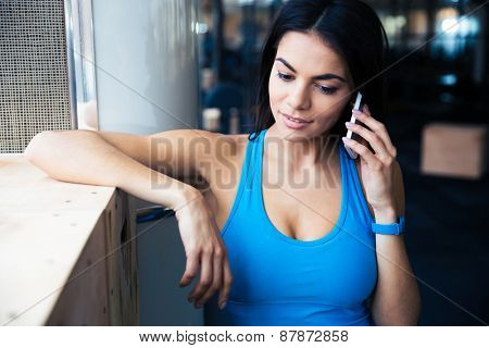 Beautiful fit woman talking on the phone at gym