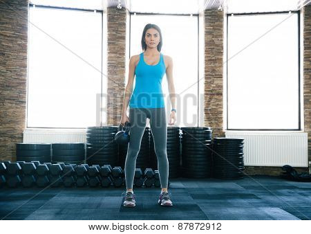 Beautiful young woman working out with kettle ball at gym