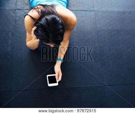 Fit woman lying on the floor with smartphone