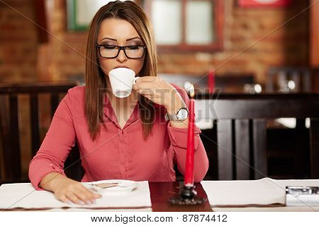 Young Woman Drinking Coffee In A Restaurant