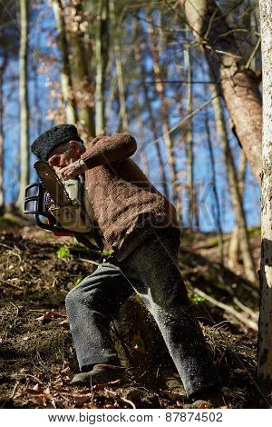 Senior Man With Chainsaw In A Forest