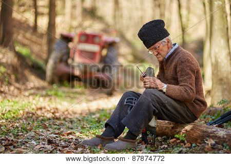 Senior Farmer Servicing His Chainsaw After Use