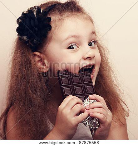 Happy Cute Beautiful Kid Girl Biting Sweet Chocolate. Vintage Portrait