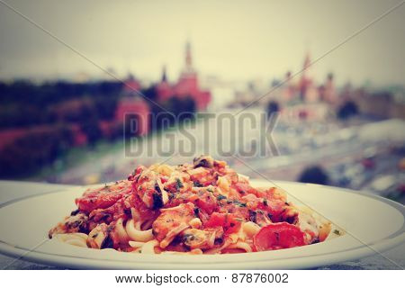 Fried mussels with pasta, Moscow Kremlin in the blurred background, toned image