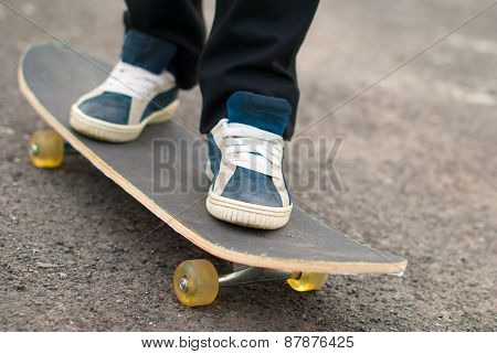 Skateboarder Feet In Sneakers On A Skateboard.