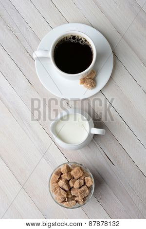 High angle shot of a cup of coffee, cream pitcher, and a bowl of natural sugar cubes. Vertical format on a rustic whitewashed table.