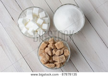 Three glass bowls filled with granulated sugar, white sugar cubes and natural sugar chunks. High angle view on a rustic wood kitchen table.