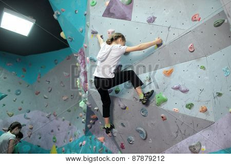 DNEPROPETROVSK, UKRAINE - APRIL 11, 2015: Girls train during the open bouldering festival Dnepr Montana Kids. The festival organized by the climbing wall Montana and the association of extreme sports