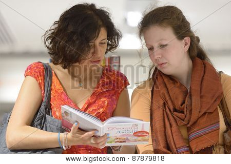 MOSCOW, RUSSIA - JULY 30, 2013: Women read the book of French dietitian Dr. Pierre Dukan during the meeting with readers of the magazine Marie Claire in Moscow, Russia on July 30, 2013