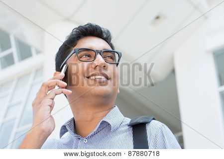 Indian businessman talking on phone in front modern office building.