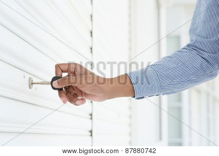 Male hand inserting key in keyhole to opening locked metal door.