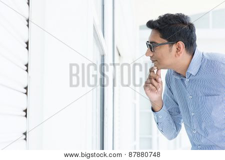 Young Asian man looking through the window and thoughtful.