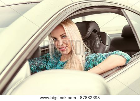 Attractive young blond woman driving the auto