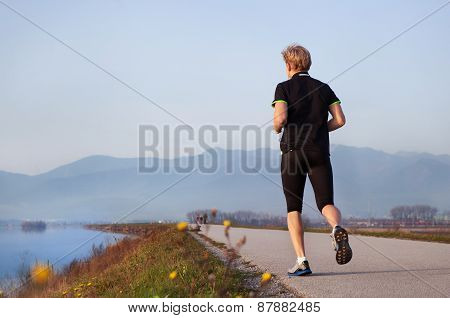Young Man Jogging Near The Lake