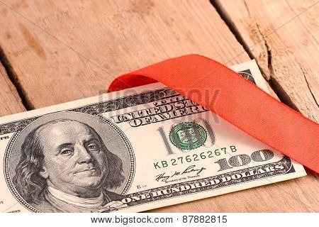One Hundred Dollar Bills Wrapper In Red Ribbon