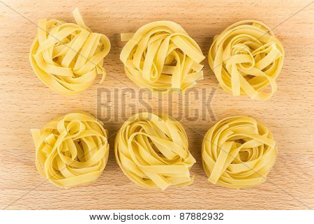 Pasta In Form Nest On Wooden Board