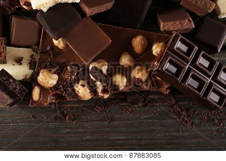 Set of chocolate with hazelnut on wooden table, closeup
