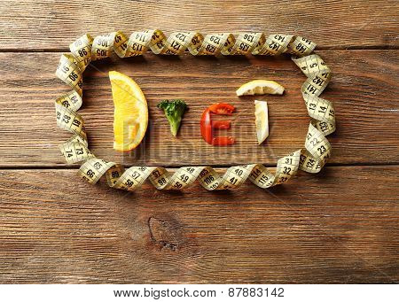 Word DIET made of sliced vegetables with measuring tape on wooden background