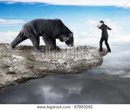 Businessman Against Black Bear Balancing On Cliff With Sky Cloudscape