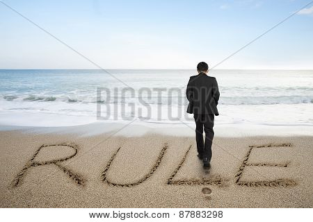 Rear View Businessman Standing With Rule Word On Sand Beach