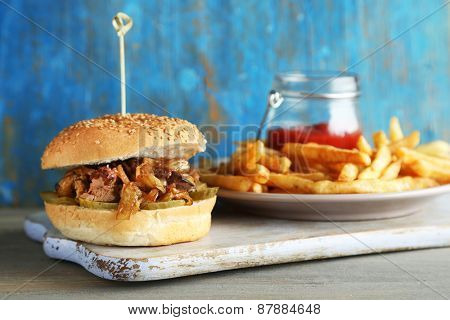 Tasty sandwich on cutting board, on color wooden background. Unhealthy food concept