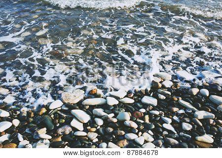 Pebble beach and waves. Shallow sea.