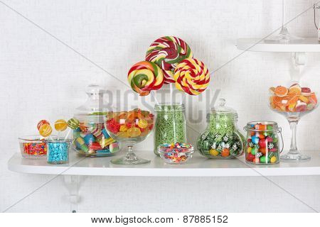 Colorful candies in jars on shelves close-up