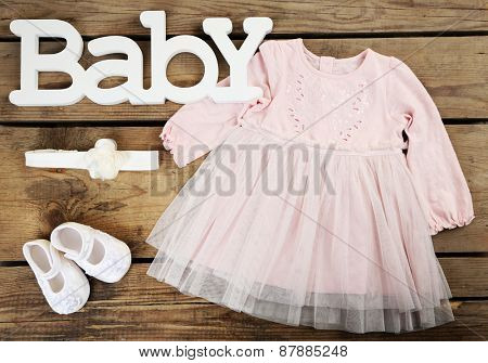 Clothes for baby girl on wooden background