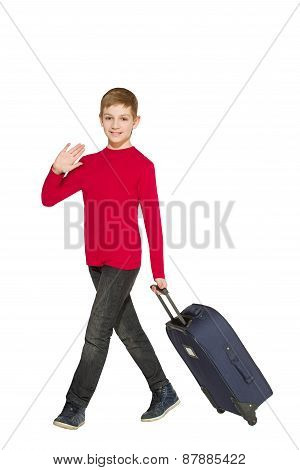 Smiling boy walking and waving hello holding travel bag