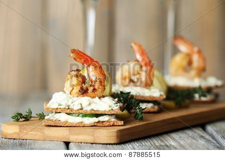 Appetizer canape with shrimp and cucumber on plate on table close up