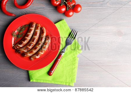 Grilled sausages on plate with vegetables on table close up