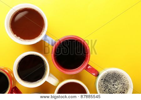 Many cups of coffee on color table, top view